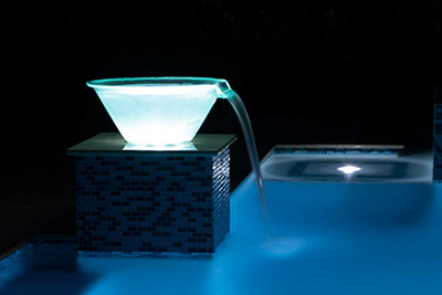 Blue light-up water bowl installed over inground swimming pool by Seaway Pools